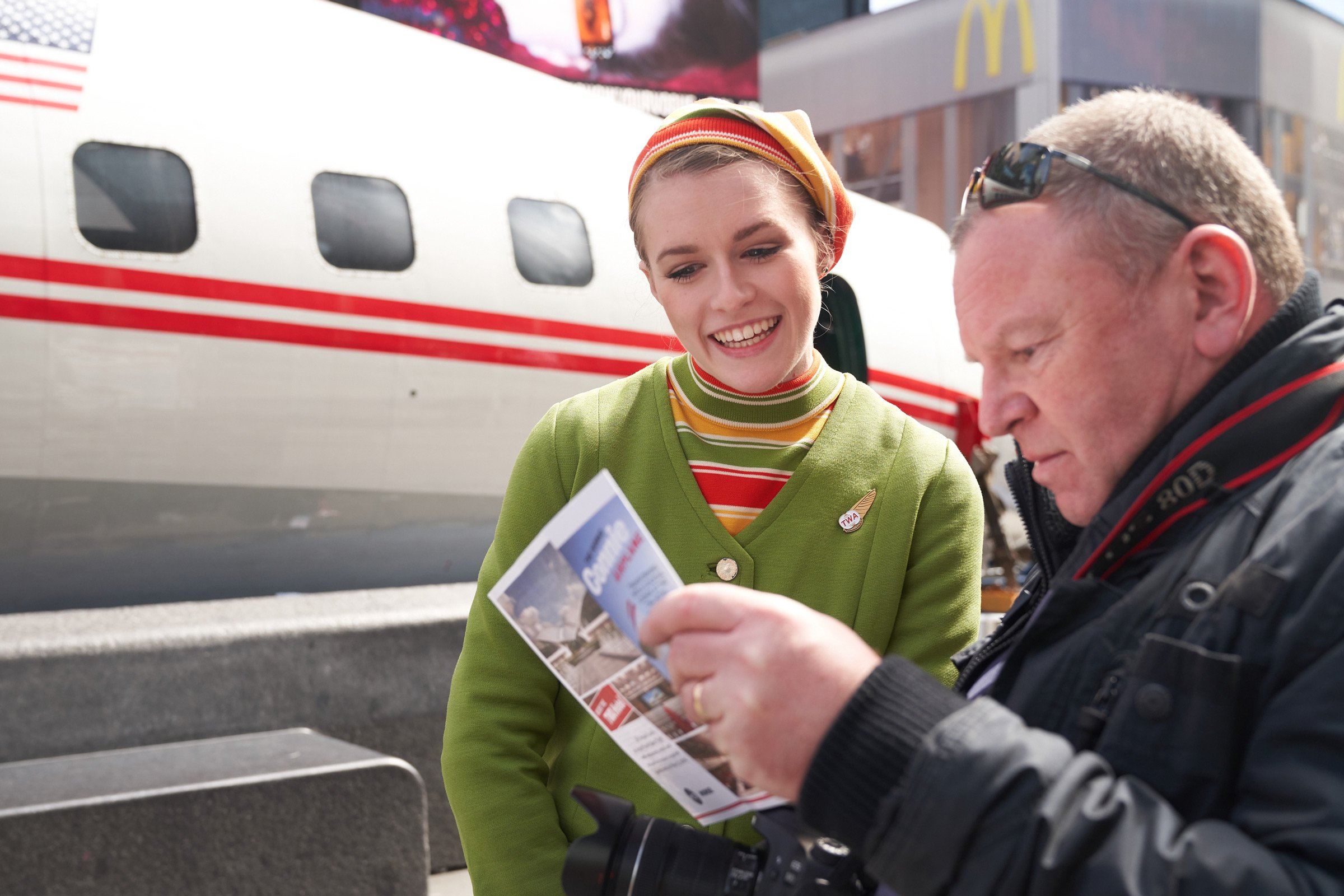 An actress in a vintage TWA flight attendant uniform educates a passerby about Connie's storied history on March 24, 2019.